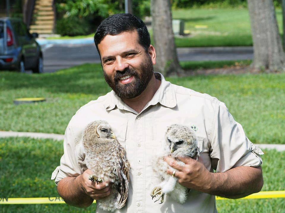 An image of the founder, Wayne, holding two owls.